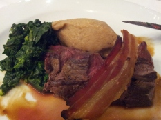 Roasted venison loin with crispy pancetta and walnut mash, with spinach. At Caravaggio, London